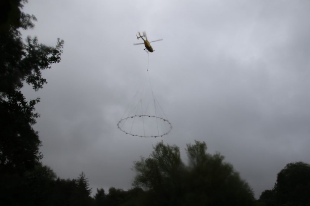 Helicopter installing fountain in the lake